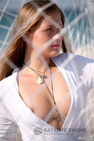 Обнаженная круглолицая девчонка с кулоном на груди