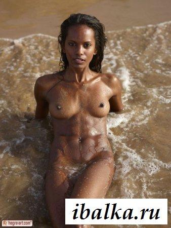 Худенькая раздетая негритянка развлекается в море