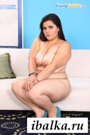Толстуха сидя на диване мнет киску